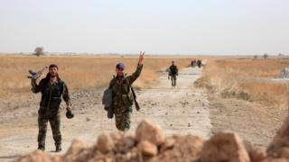 Syrian soldiers gesture as they walk down a road near Kweyris military airport, in Aleppo province (18 October 2015)