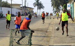 Footballers play a game on a street in central Monrovia, Liberia - Sunday 15 January 2017
