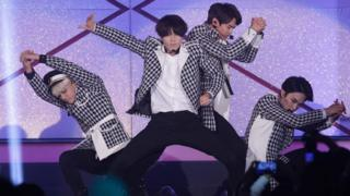 Korean pop band Shinee dancing on stage