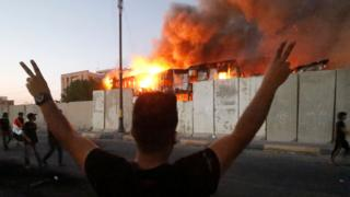 A protester stands with arms raised in front of a burning government building in Basra, 6 September 2018
