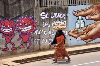 A woman walks past graffiti on a wall depicting hygiene measures to curb the spread of Covid-19 in Conakry, Guinea.