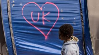 "Child walks past a tent in Calais Jungle which has ""UK"" in a love heart written in graffiti"