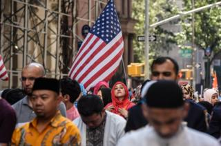 People participate in a group prayer in the street before the start of the annual Muslim Day Parade in New York City, US on 24 September 2017.