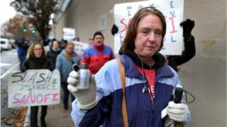 Alec Smith's mother holds a vial of her son's ashes during a protest against the high price of insulin outside Sanofi's offices in Massachusetts