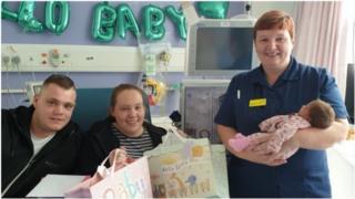 """الأم الجديدة إيلي، مع الأب دان تايلور والممرضة بوبي بيدفورد التي تحمل الطفلة """"المعجزة"""""""