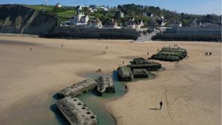 In this aerial view pontoons from the World War II Allied temporary Mulberry harbor built during the D-Day invasion lie on the beach on April 30, 2019 at Arromanches-les-Bains,