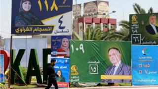 A man walks next to election campaign posters in Baghdad, Iraq