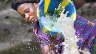 Woman scooping water (Image: Rachel Agnew/Rainforest Foundation UK)