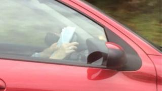A submitted picture of a driver reading at the wheel