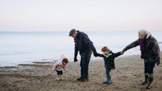 an older couple on a beach with some children