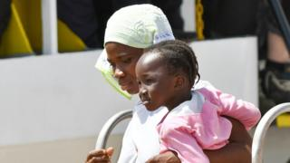 Mother and child from Africa disembarking in Italy