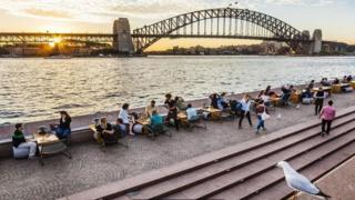 أستراليون يجلسون لتناول مشروباتهم بالقرب من النهر