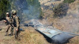Pakistani troops guard wreckage of an Indian plane, February 2019