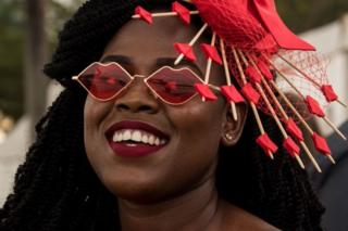 A woman wearing an intricate red fascinator and red, lip-shaped sunglasses smiles.