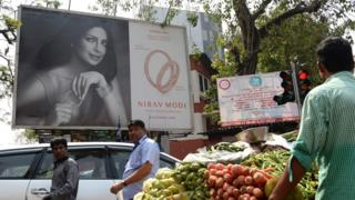 Indians walk past a billboard with a picture of Bollywood actress Priyanka Chopra promoting the luxury jewellery store Nirav Modi in Mumbai on February 15, 2018