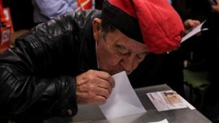 Man in traditional Catalan cap votes