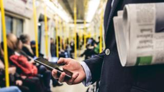 Una persona usando el celular en el transporte público.