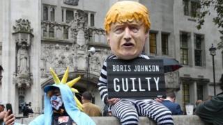 مردی در لباس بوریس جانسون با پلاکارد 'مجرم' در مقابل دیوان عالی بریتانیا