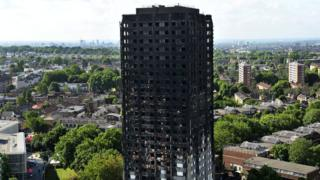 The charred remains of Grenfell tower, West London, as seen from a height, with a panorama of leafy West London behind it.