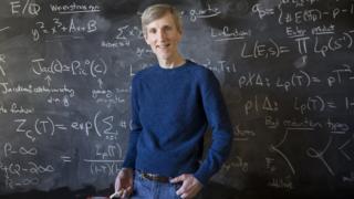 O matemático Andrew Sutherland em frente a um quadro negro em que há uma série de cálculos escritos a giz