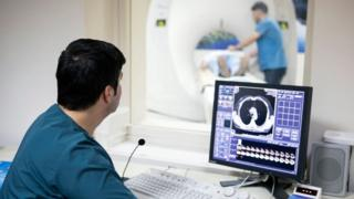 A generic picture of a doctor analysing a scan while a patient is in a scanner