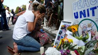 A woman reacts at a make shift memorial outside the Al-Noor mosque in Christchurch