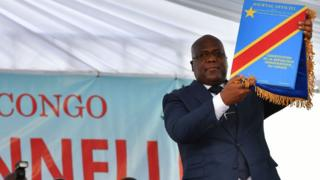 Democratic Republic of the Congo's newly inaugurated President Felix Tshisekedi raises an official copy of the nation's constitution on January 24, 2019