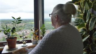 Pat enjoys the view from her tower block window