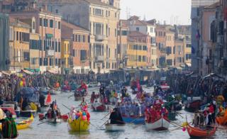 Venetians row during the masquerade parade on the Grand Canal.