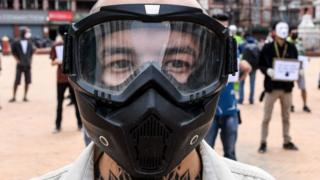 A protester wears a full-face mask during a demonstration against the government's handling of the fight against the COVID-19 coronavirus in Kathmandu on June 12, 2020