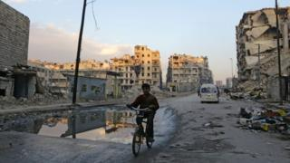 A Syrian boy rides his bicycle past destroyed buildings in Aleppo's formerly rebel-held al-Shaar neighbourhood on 21 January 2017, a month after government forces retook the northern Syrian city from rebel fighters