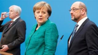 German Chancellor Angela Merkel, Christian Social Union (CSU) leader Horst Seehofer and Social Democratic Party (SPD) leader Martin Schulz stand on stage in an off-guard shot