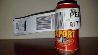 The can wrapped in a Qantas baggage tag