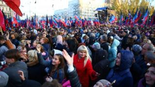 Crowds of people wave flags and hold up phones in the Donetsk Republic as they await their acting leader, Denis Pushilin