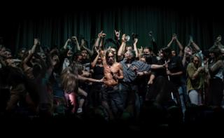 Iggy Pop dances with the audience on stage