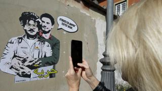 "A woman takes a picture with a mobile phone of a mural believed to be made by street artist Laika portraying Patrick George Zaky (L) wearing an inmate's uniform and being embraced by Giulio Regeni (R) with the words: ""This time everything will be fine"" (top) and ""Freedom"" (bottom), written in Arabic, on a wall surrounding Villa Ada, a few steps from the Embassy of Egypt, in Rome, Italy - Tuesday 11 February 2020"