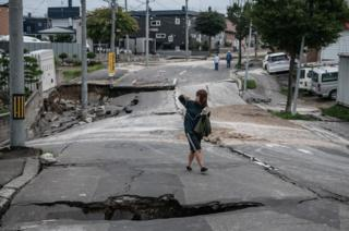 A woman takes a photograph as she walks along a road that was heavily damaged by an earthquake
