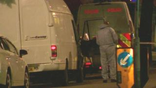 Forensic officer looking at van