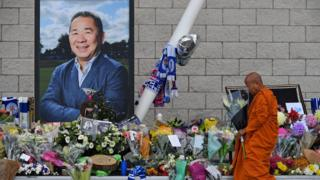A Buddhist monk lay tributes by a photograph of Leicester City Football Club's Thai chairman Vichai Srivaddhanaprabha outside the club's stadium