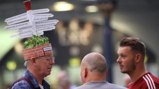 Man with road sign hat chats to visitors during the traditional hat day during the CAMRA Great British Beer Festival at Olympia in London