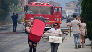 Residents carry belongings in Lake Elsinore, California, south-east of Los Angeles, on August 10, 2018