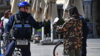 A municipal police officer controls a passer-by for her certificate as they monitor people's movement in Montpellier, 25 March 2020