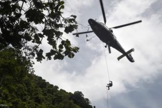 A Thai Airforce worker drops in by helicopter into a clearing in the forest near a possible overground opening to the Tham Luang cave