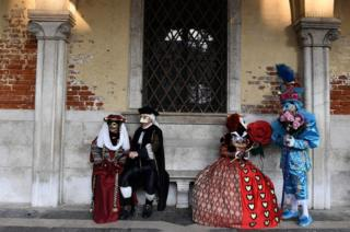 Masked revellers wearing traditional carnival costumes pose in Saint Mark's Square during Venice's Carnival