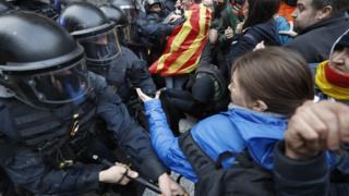 警察と衝突するデモ参加者ら(25日、スペイン・バルセロナ)