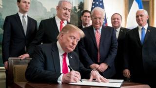 Trump firmando documento con Netanyahu.