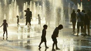 Children play in the water fountains at the Place des Arts in Montreal, Canada on a hot summer day July 3, 2018.