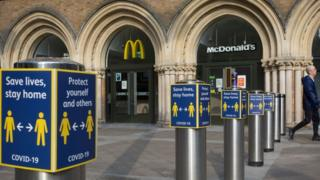 A man walks past the McDonald's restaurant in Liverpool Street Station, with social distancing signs outside