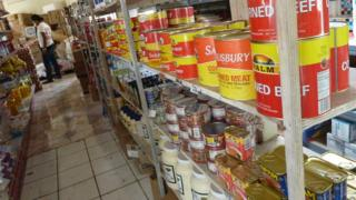 Cans of imported corned beef and other processed meat on a supermarket shelf in Tonga
