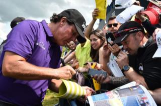 Fans look on as Phil Mickelson signs a prostehtic leg at Royal Portrush